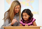second grade writing - teacher helping girl at her desk