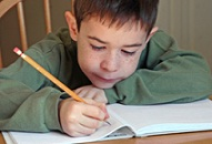 first grade boy writing on a worksheet