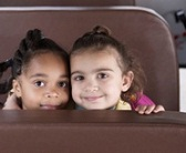 two first grade girls sitting together on a school bus