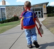 1st grade boy walking into school with backpack and lunch bag