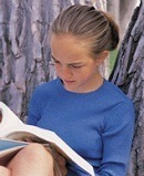 girl sitting under a tree studying her spelling words
