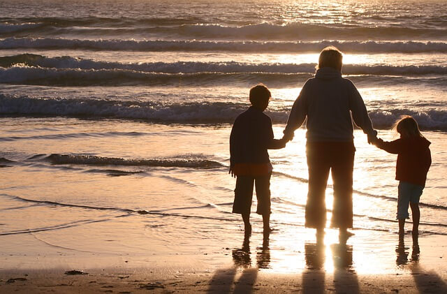 family walking at sunset on beach