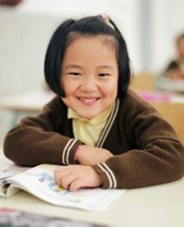 smiling first grade girl sitting at her desk