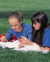 two girls studying together outside on the lawn