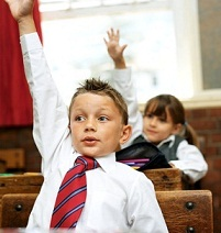 boy in classroom raising his hand