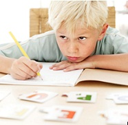 first grade boy with chin on his hand, doing schoolwork