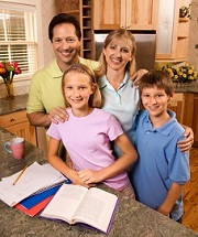 smiling home school family with books open at the kitchen counter