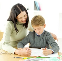woman teaching young boy at his desk