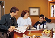 family at table doing school work and reading the newspaper