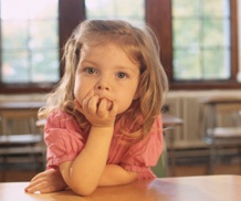 preschool girl leaning on desk