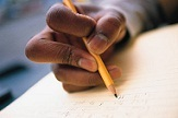 student's hand, writing on his paper