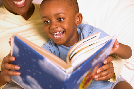 little boy on mom's lap enjoying a picture book
