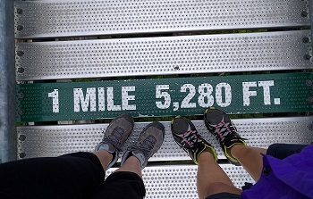 two pairs of feet standing on a sign that reads 1 MILE - 5280 Ft.