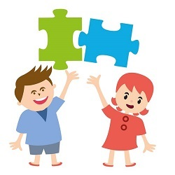 Two smiling students holding up jigsaw puzzle pieces