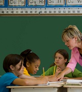 teacher helping students with worksheets