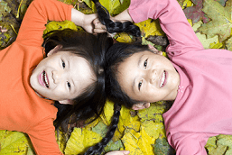 two girls in a pile of leaves