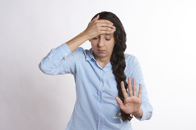 Stressed out young woman, holding her head and pushing her hand out in front of her